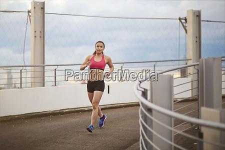 young female asian sportswoman jogging