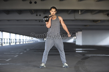 sportive man training with kettlebell