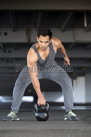 muscular man training with kettlebell