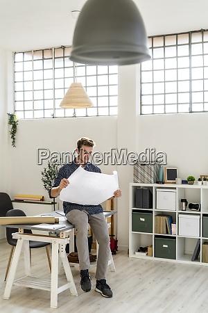 architect reading blueprint while sitting on