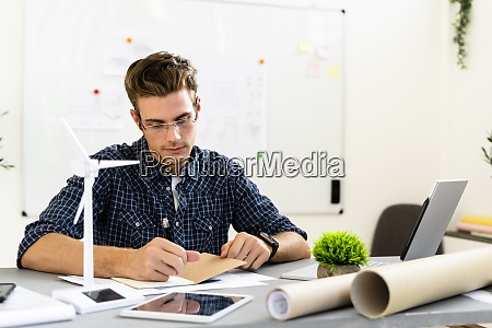 young man writing while working by