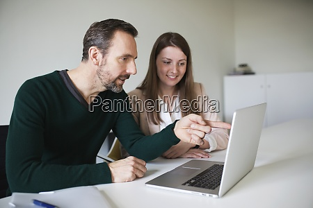 businessman and employee using laptop at
