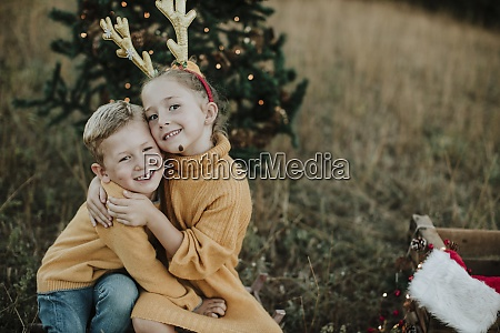smiling siblings embracing while sitting by