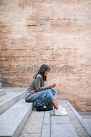 young woman using smart phone while