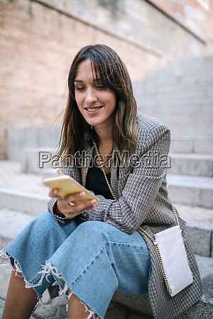 young woman smiling while using smart