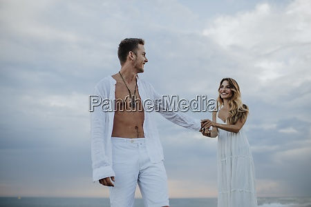 smiling woman holding hand of man