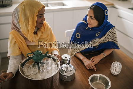 female friends preparing tea while sitting