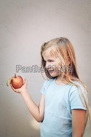 cute blond girl holding fresh organic