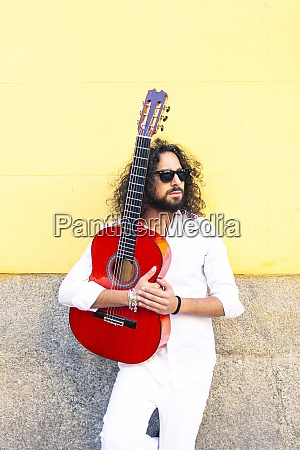 man holding guitar while standing against
