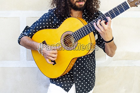 man playing guitar while standing against