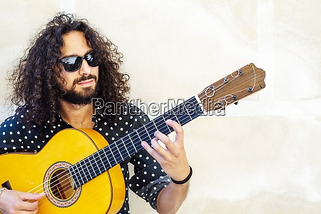 man with sunglasses playing guitar while