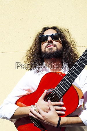 guitarist holding guitar while standing against