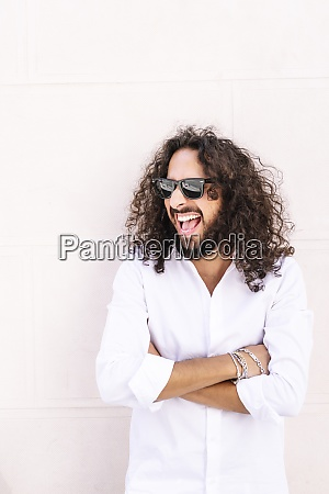 man with arms crossed laughing while