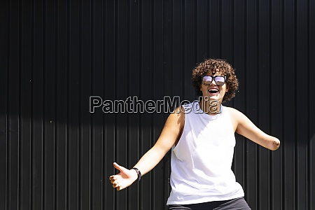 happy amputee boy dancing against shutter