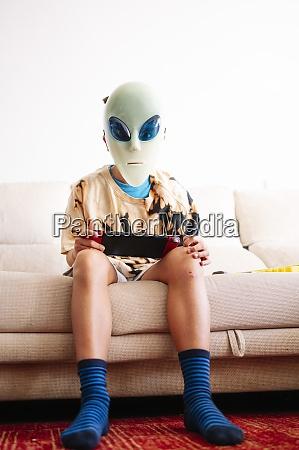 boy wearing alien mask playing handheld