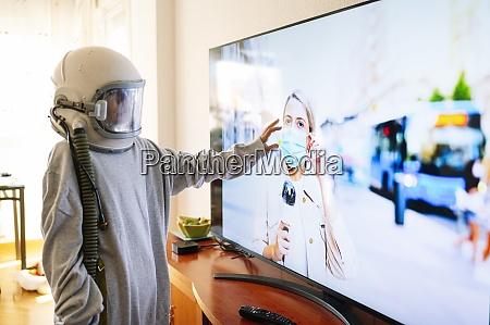 boy wearing space helmet touching journalist
