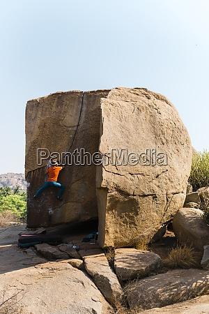 male rock climber ascending huge boulder