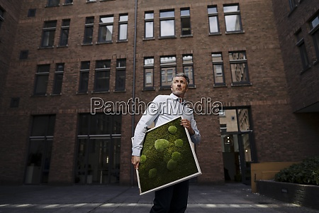 businessman carrying moss frame while standing