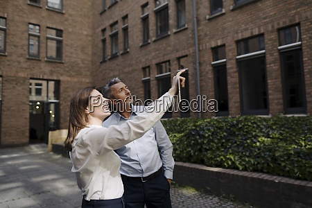 woman pointing while standing by businessman