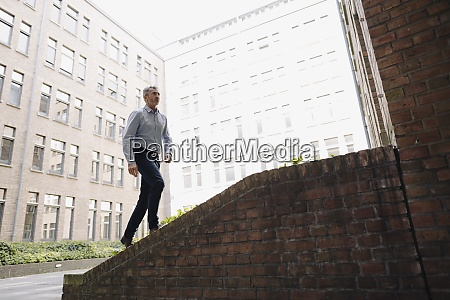 businessman walking on staircase against building