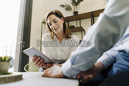 smiling woman using digital tablet while