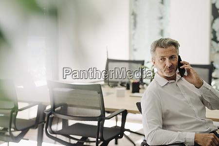 businessman talking on phone while sitting