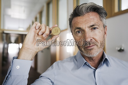 businessman holding bitcoin in hand at