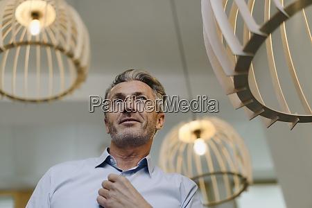 businessman standing by illuminated light fixture