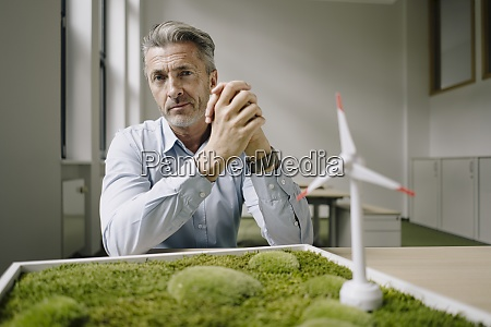 businessman with hands clasped sitting by