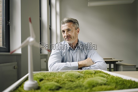 smiling businessman sitting by wind turbine