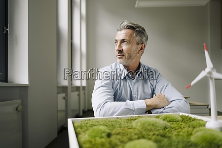 businessman looking away while sitting by
