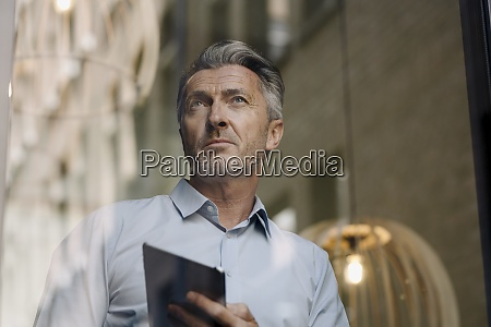 man using digital tablet while standing