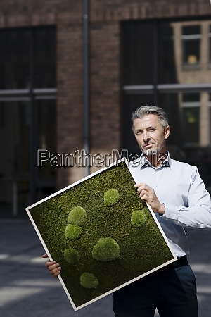 businessman holding moss frame while standing