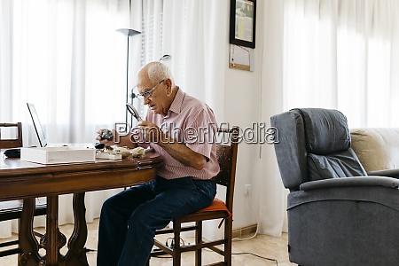 retired elderly man using magnifying glass