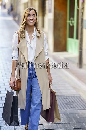 woman carrying shopping bag while walking