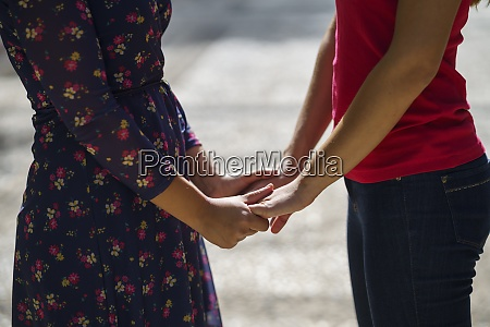 women holding hands while standing on