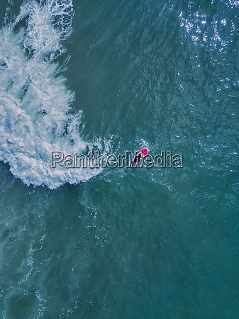 aerial view of young womanpaddleboardingin sea
