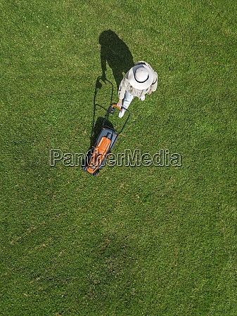 woman with lawn mower standing on