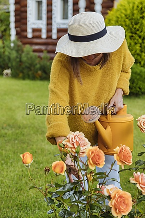 woman with hat examining rose while
