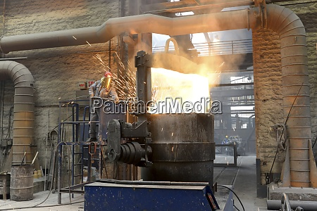 worker checking temperature of material in