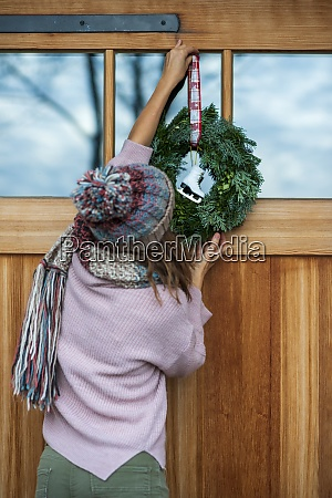 young woman hanging wreath on house