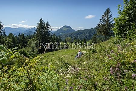 senior woman relaxing in alpine meadow