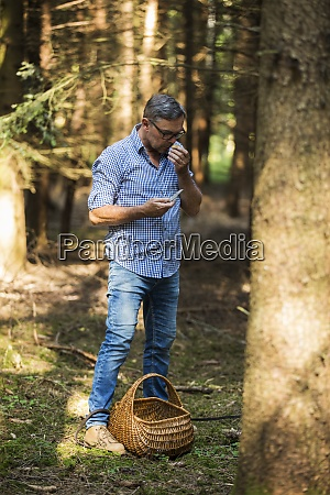 man tasting mushroom while standing in