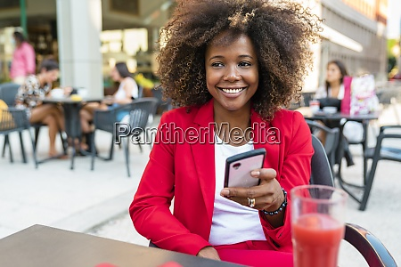smiling woman text messaging while sitting