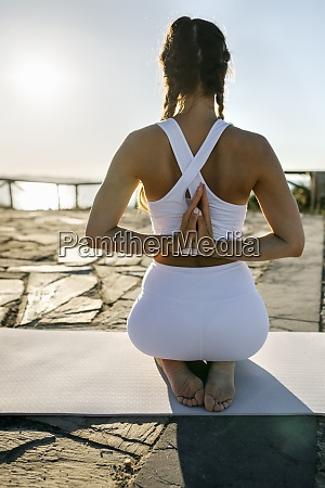 young woman practicing prayer pose on