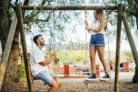 young couple spending time on swings
