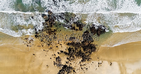 aerial view of rocks on sandy
