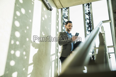 young businessman in staircase looking on