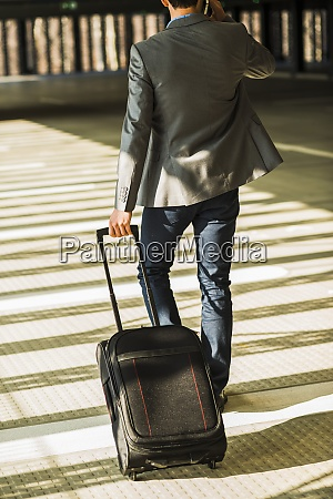 young businessman with baggage walking in