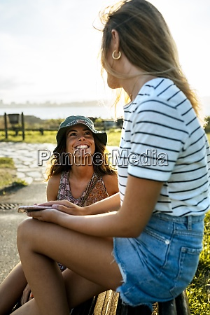 smiling young women talking while spending